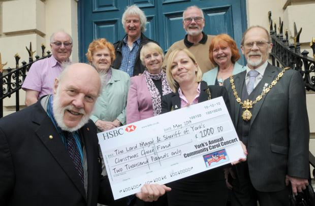 Carol Concert chairman John Warburton, front, presents the cheque, for the Christmas Cheer Fund, to the Lord Mayor Cllr Julie Gunnell, and Sheriff Brian Watson, watched by Carol Concert committee members at the Mansion House