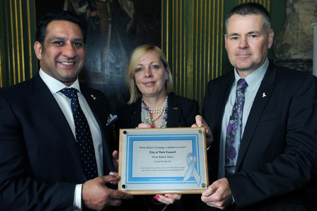 Sports ambassador Ikram Butt (left) presents the White Ribbon Status plaque to the Lord Mayor of York, Cllr Julie Gunnell, with Andrew Overton at the Mansion House.