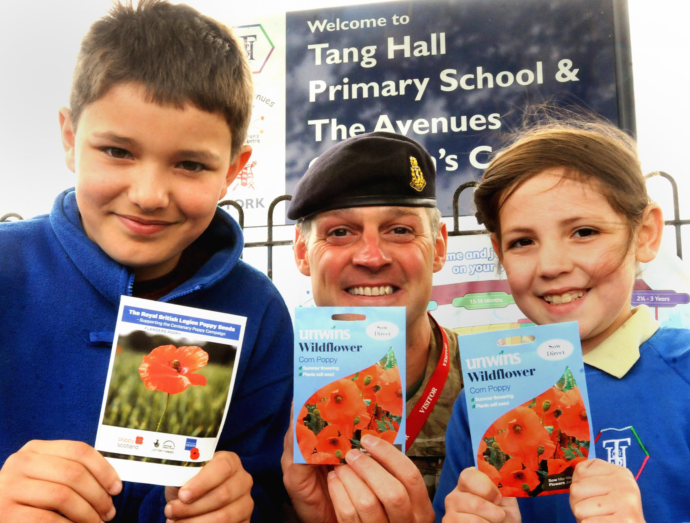 WO1 RSM Andrew Hiley with Tang Hall Primary School pupils Yonese and Gracie, holding packets of poppy seeds which were planted in the school grounds in order that they will flower in late August to mark the centenary of World War 1.