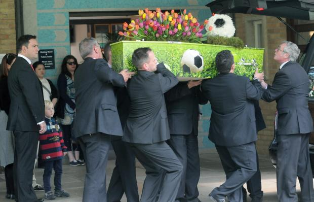 York Press: Oscar Hughes's coffin is carried into York Crematorium, watched by his father Ian and brother Lucas
