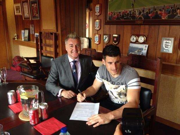 Michael Coulson signs his new deal at York City watched by chairman Jason McGill