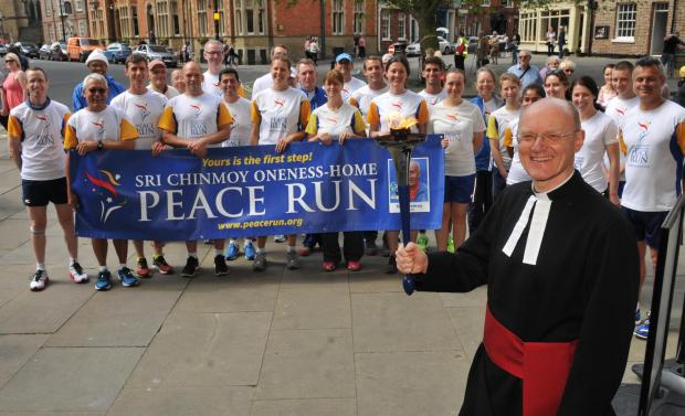 Canon Chris Collingwood holds the torch of peace as the runners call at York Minster