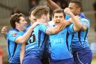 Pat Smith celebrates another try and is mobbed by delighted team-mates