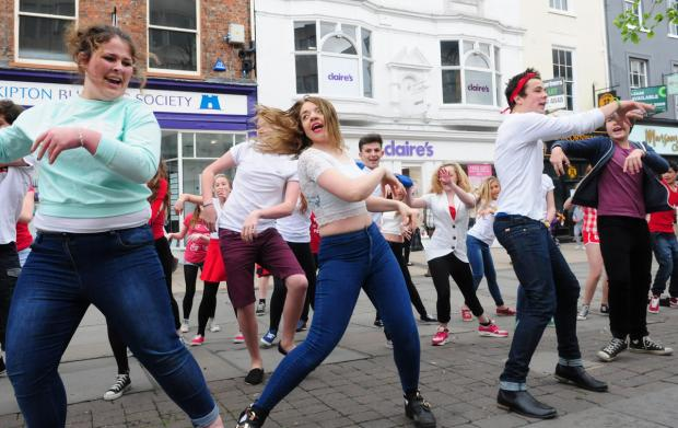 the cast of York Light Youth's production of High School Musical perform for the bank holiday crowds in Parliament Street