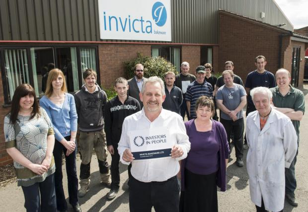 Smiles all round for staff at Invicta Bakeware. John Waddington, managing director, displays the prestigious Investors in People award.
