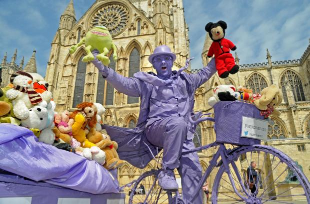Purpleman with some of the 1,000 soft toys donated by Y