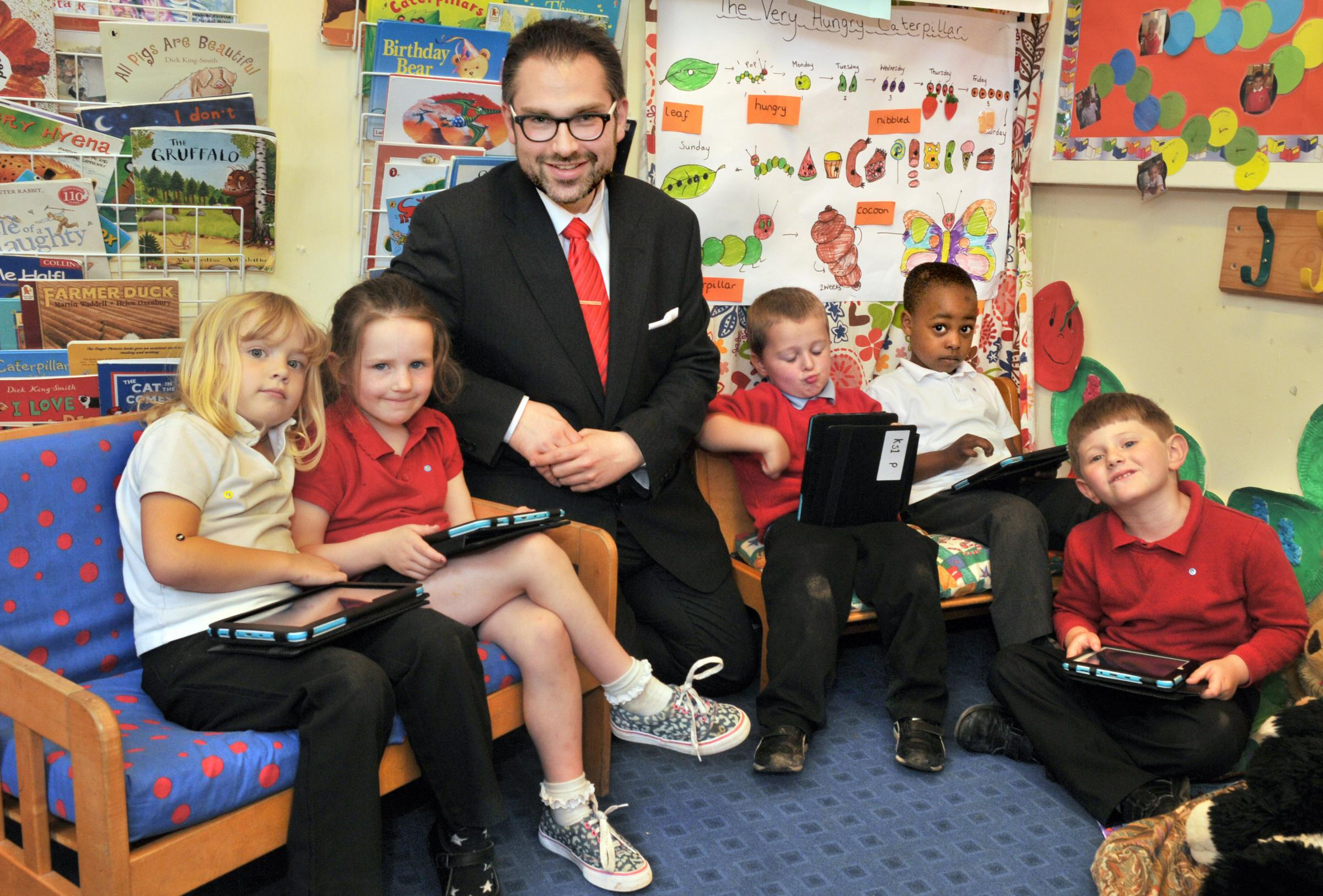LEARNING CURVE: Coun James Alexander with pupils at Burton Green Primary School and their new tablets.                      Picture: Nigel Holland