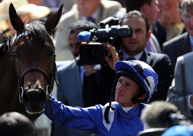 Taghrooda is patted by its jockey Paul Hanagan