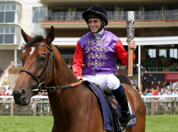Ryan Moore with the Queen's Baton as he rides D'arcy Indiana at Newmarket