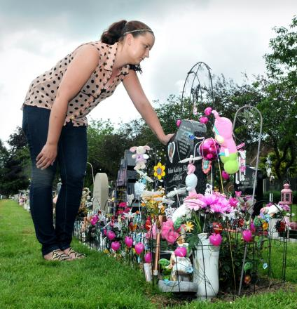 Kia Carlton at the grave of her baby daughter, Telan