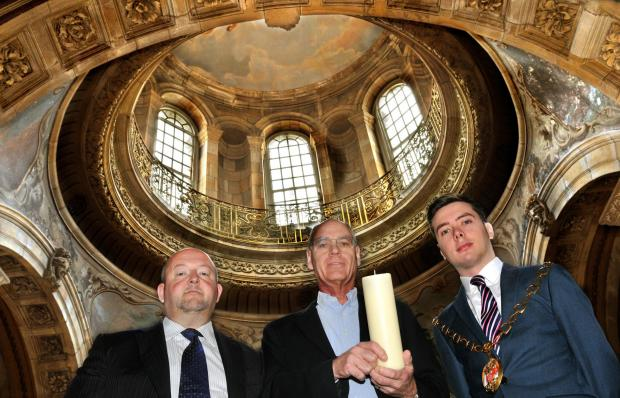 Simon Howard holds a candle to commemorate the centenary of Lights Out In Ryedale at the declaration of the First World War watched by, left, Julian Rudd and Cllr Luke Ives.