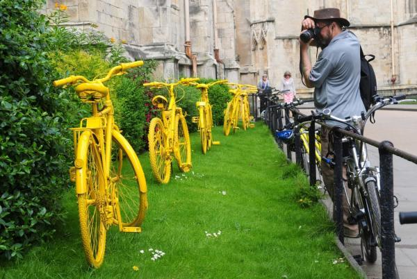A tourist takes a picture of a row of yellow bikes outside St Michael Le Belfrey church