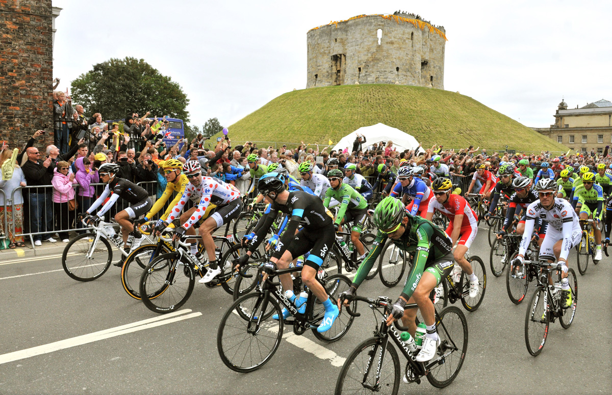 Riders pass Clifford's Tower in York earlier today