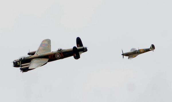 The Lancaster bomber and Spitfire of the Battle of Britain Memorial Flight pass over York Racecourse before the start of the Tour de France