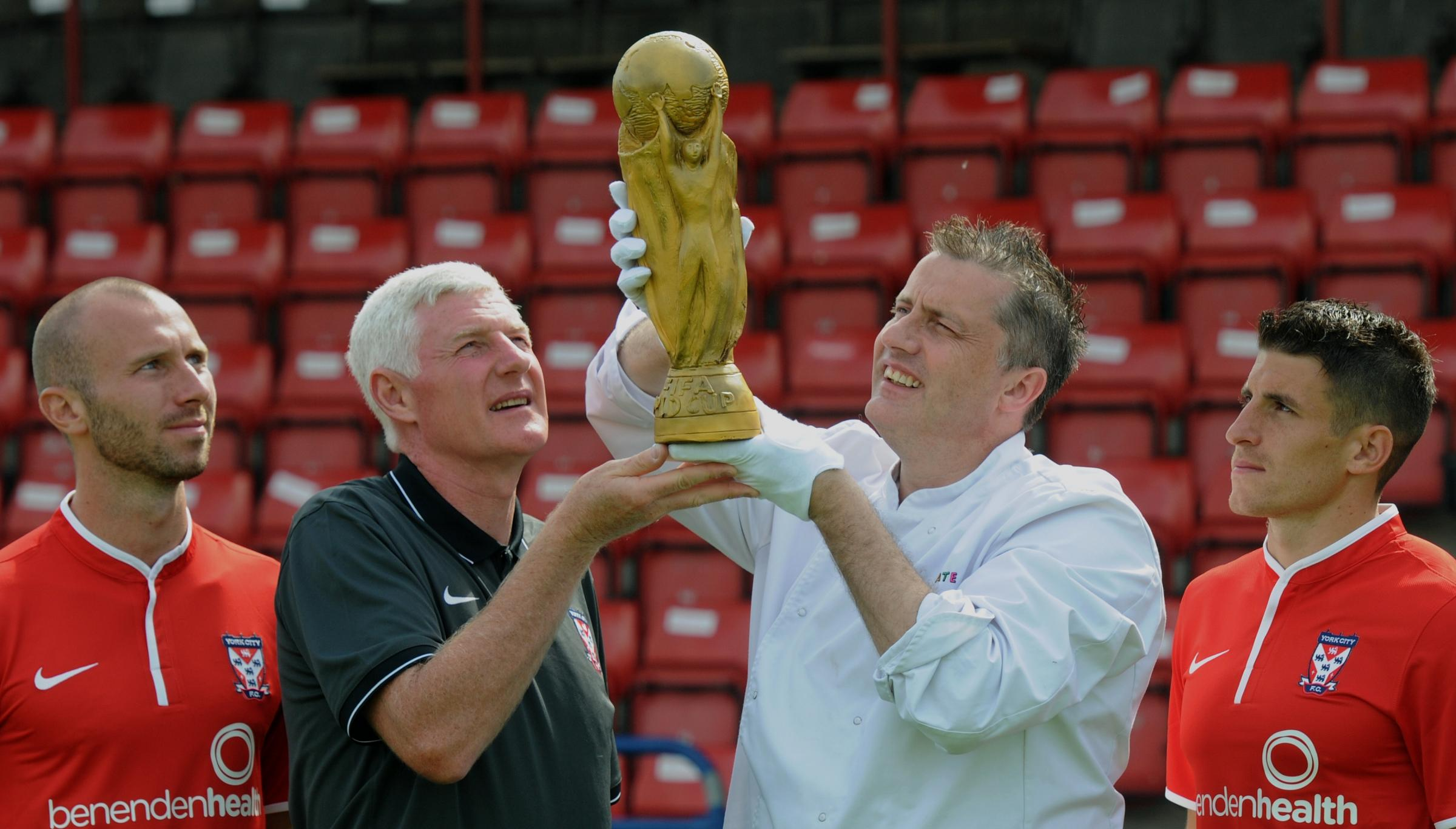 York City manager Nigel Worthington gets a closer look at the chocolate World Cup, held by York Chocolate Story's head chocolatier Andrew Thwaite, wa