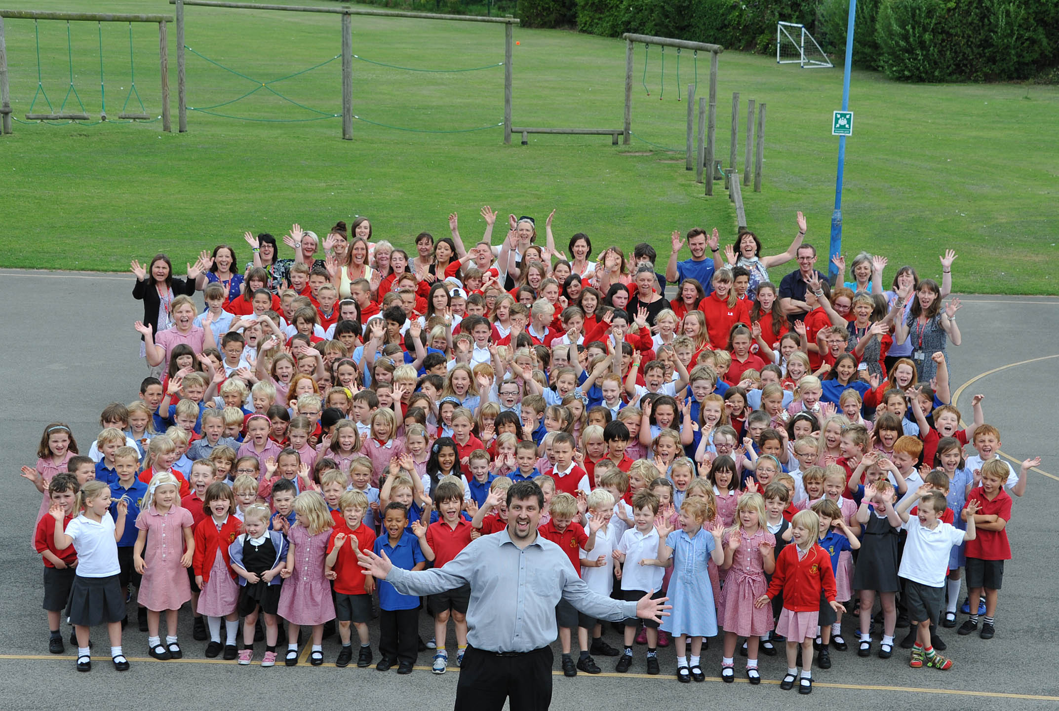 Headteacher Lee Haynes and pupils and staff at Acomb Primary School celebrating their Ofsted success.
