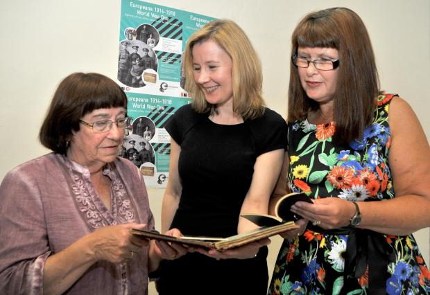 Carol Smith, from Selby, Eleanor Kenny, from the Europeana Archive, and Jeanette Payne, from Leeds, look at an autograph book containing the signatures of wounded servicemen obtained by Carol's maternal grandmother as she worked as a nurse during the wa