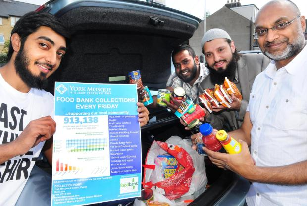 Hakeem Hussein, front, Ismail Miah, Abid Salik and Mebs Surve with food bound for the food bank
