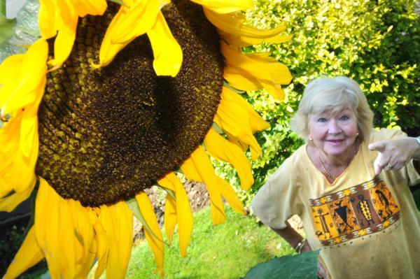 Ren Entwistle, from Ampleforth, with her giant sunflower which has reached a height of 11ft 7ins