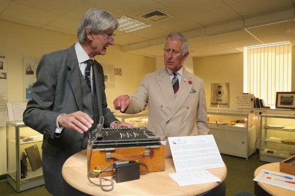 A former GCHQ historian explains the workings of an Enigma coding machine to the Prince of Wales as he tries one out in the museum of GCHQ Scarborough in Scarborough. Picture: Christopher Furlong/PA Wire