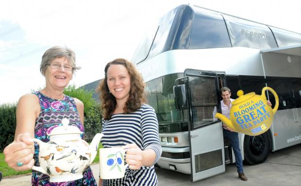 Preparing for the Marie Curie Bloomin Great Tea Party are, left to right, Karen Kemp and Natalie Atherley, community fundraiser, and Ollie Kemp with his renovated bus