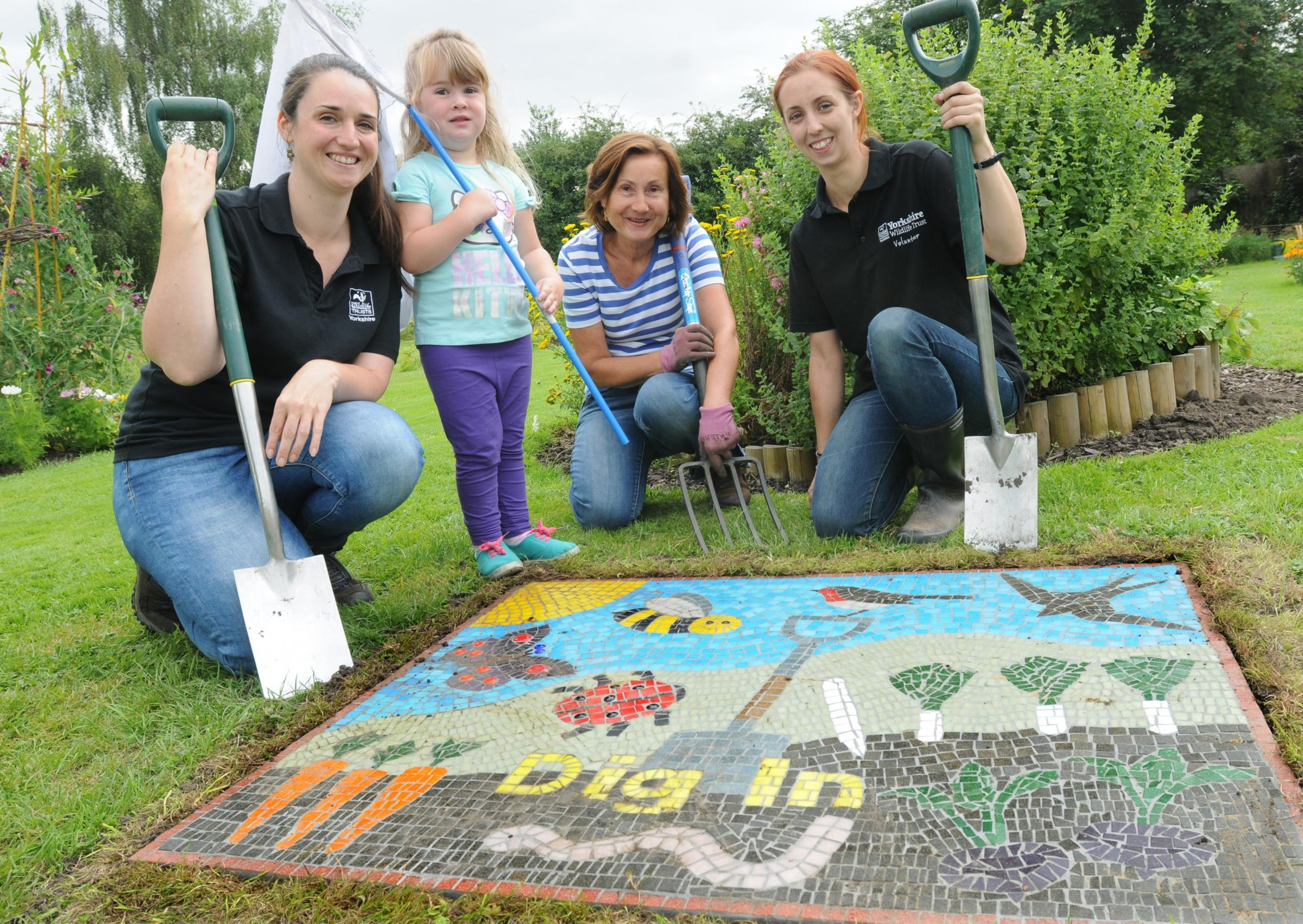 The new mosaic at the Yorkshire Wildlife Trust's Glen Community Garden, Heworth , is shown off by Marie Birbeck, Mya Brownbridge, aged four, Selina Gee and Jess Wharf