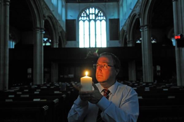St Michael le Belfrey administrator Mark Rance lights a candle to mark the 100th anniversary of the start of the First World War