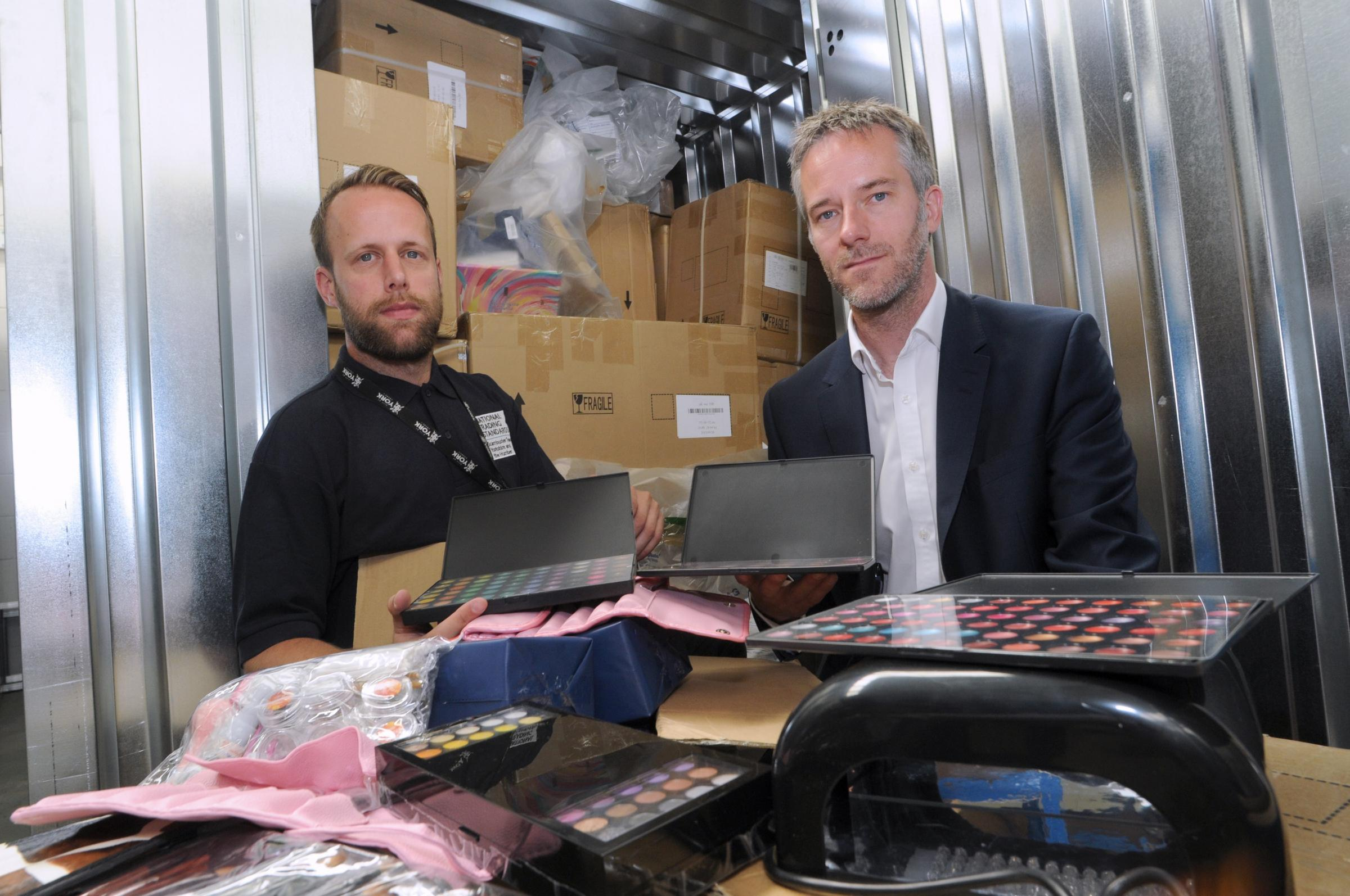 Richard Storey, left, and Mike Andrews, of the National Trading Standards eCrime Team, with a haul of fake make-up