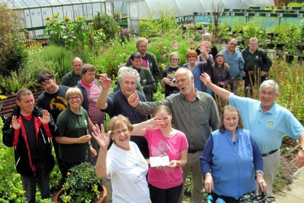 Staff and volunteers at Brunswick Organic Nursery celebrate receiving the cheque for £1,000 from York Ainsty Rotary Club president Chris True, front left
