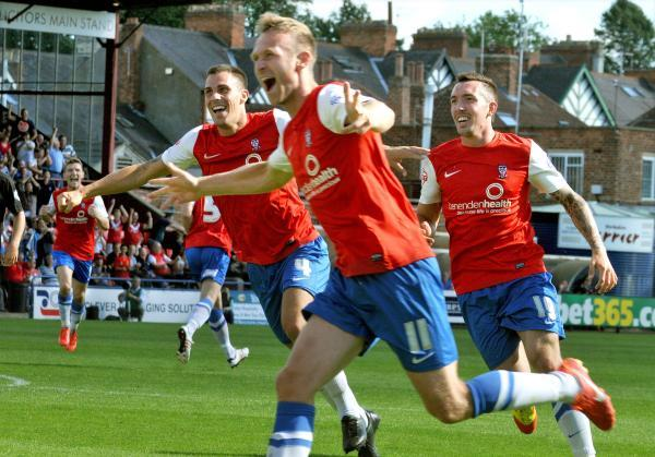 Marksman Ryan Jarvis, centre, is joined in jubilation by Chris Smith, left, and Ryan Bowman after scoring in last season's opening day win over Northampton