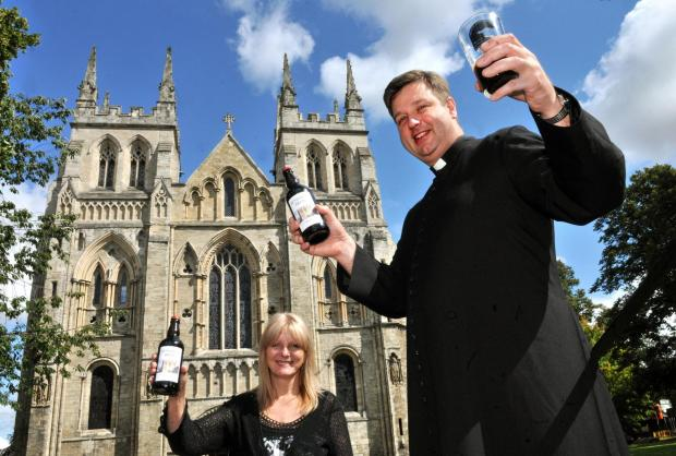Canon John Weetman celebrates with a glass of Benedict's Brew at Selby Abbey watched by Susan Simpson from the Brown Cow Brewery