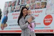 Claire Fox and her three-month-old daughter Jemima in front of the Meningitis Now billboard trailer