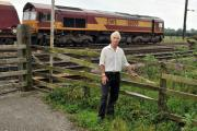 Trevor Buckle stands by a piece of broken fence at the side of the east coast main line at Copmanthorpe before it was fixed