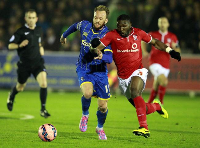 Femi Ilesanmi (R) of York races Sean Rigg for the ball during the FA Cup first-round replay between AFC Wimbledon and York City at Kingsmeadow Stadium, Kingston on Nov 18, 2014