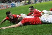 York City's Josh Carson, left, and Wes Fletcher celebrate with goalscorer Keith Lowe, foreground, at Hartlepool United