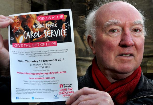 Peter Lawrence with the poster for the Missing Persons carol service
