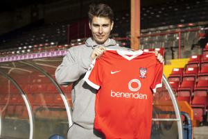 HANDY SIGNING: New long-throw ace Sam Muggleton gets to grips with a York City shirt and is now hoping to use towels to help get more distance on his missiles in the next home game