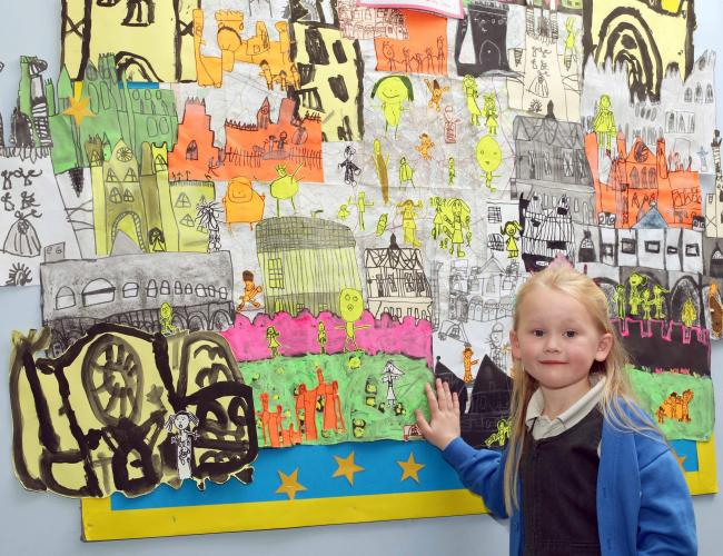 Daisy Welborn, aged six, with Rufforth Primary School's artwork