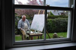George Hainsworth painting in his garden