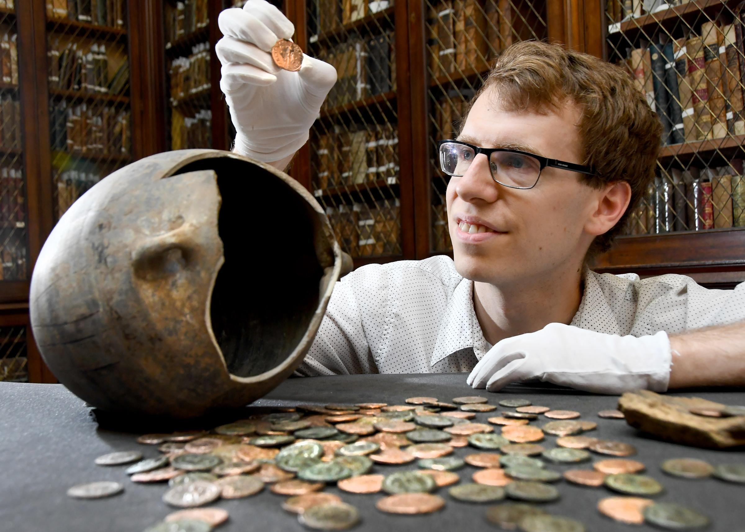 Dr Andrew Woods pictured in the historic library at the Yorkshire Museum with coins from the Wold Newton Hoard, the largest hoard of its period ever found in the North of England. Picture David Harrison.