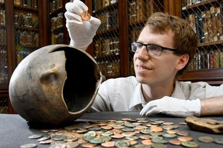 Dr Andrew Woods pictured in the historic library at the Yorkshire Museum with coins from the Wold Newton Hoard, the largest hoard of its period ever found in the North of England. Picture: David Harrison