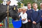 MILKING IT: Pupils at St Barnabas feed Eve the cow who visited the school, watched by farmer Paul Tompkins Picture: Nigel Holland