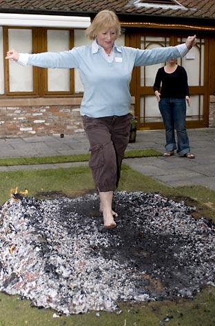 York hotel manager June Nelsey walks over hot coals in aid of Caroline's Rainbow Foundation at the Best Western Monkbar Hotel