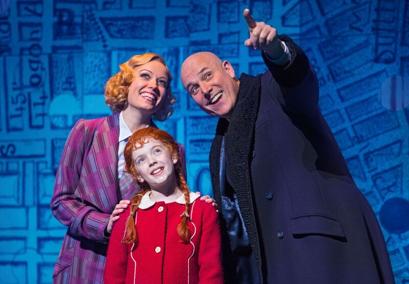 Agatha Meehan, from Kelfield, York, centre, as Annie with Holly Dale Spencer as Grace Farrell and Alex Bourne as Daddy Warbucks in Annie at the Piccadilly Theatre, London.  Picture: Darren Bell