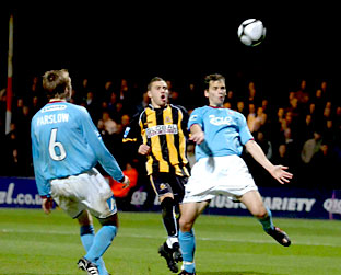 York City defender Ben Purkiss tries to cushion the ball back to 'keeper Michael Ingham under  pressure from Cambridge United's Robbie Willmott