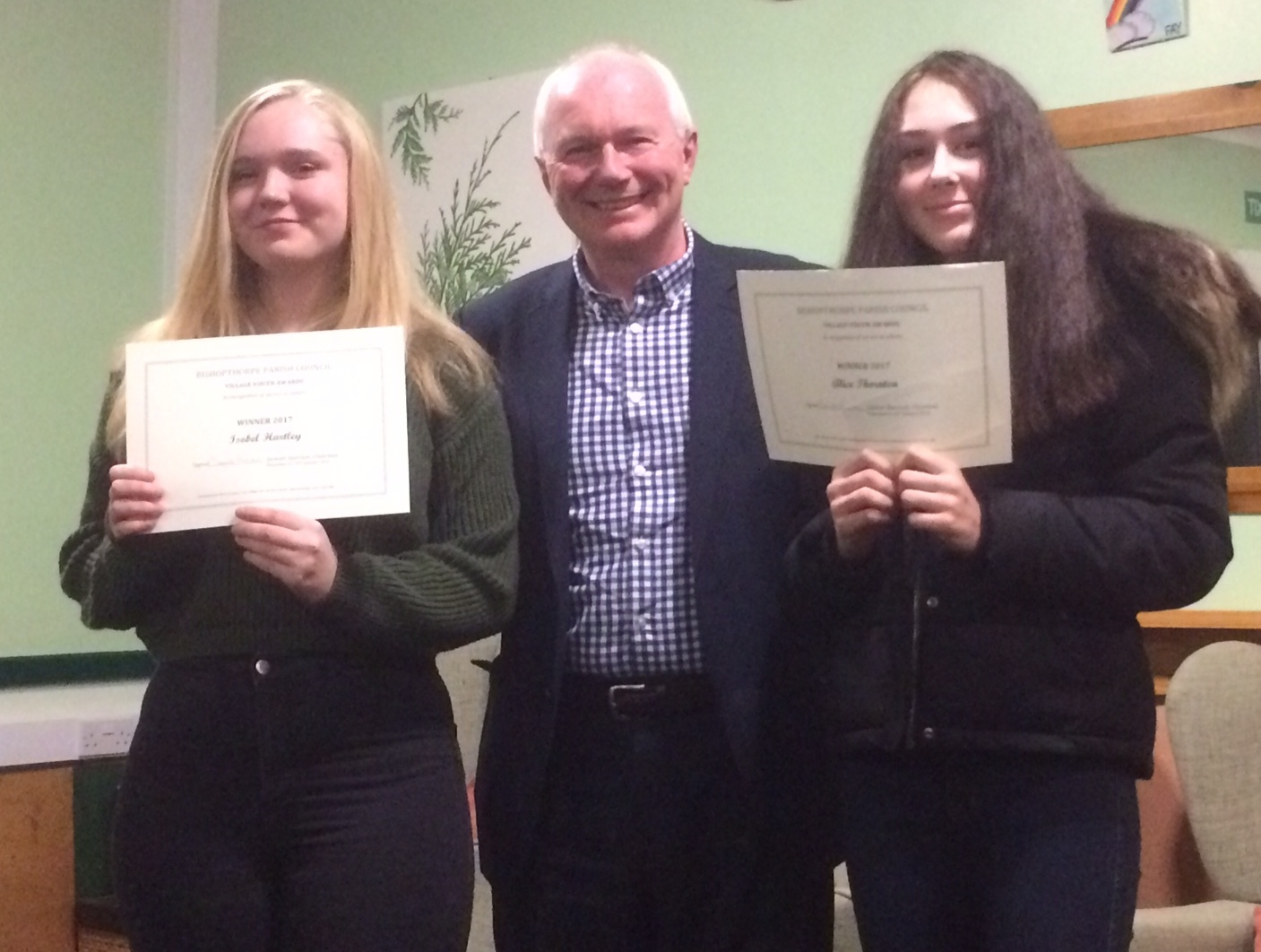 Isabelle Hartley and Alice Thornton are pictured receiving their awards from parish council chairman Stewart Harrison