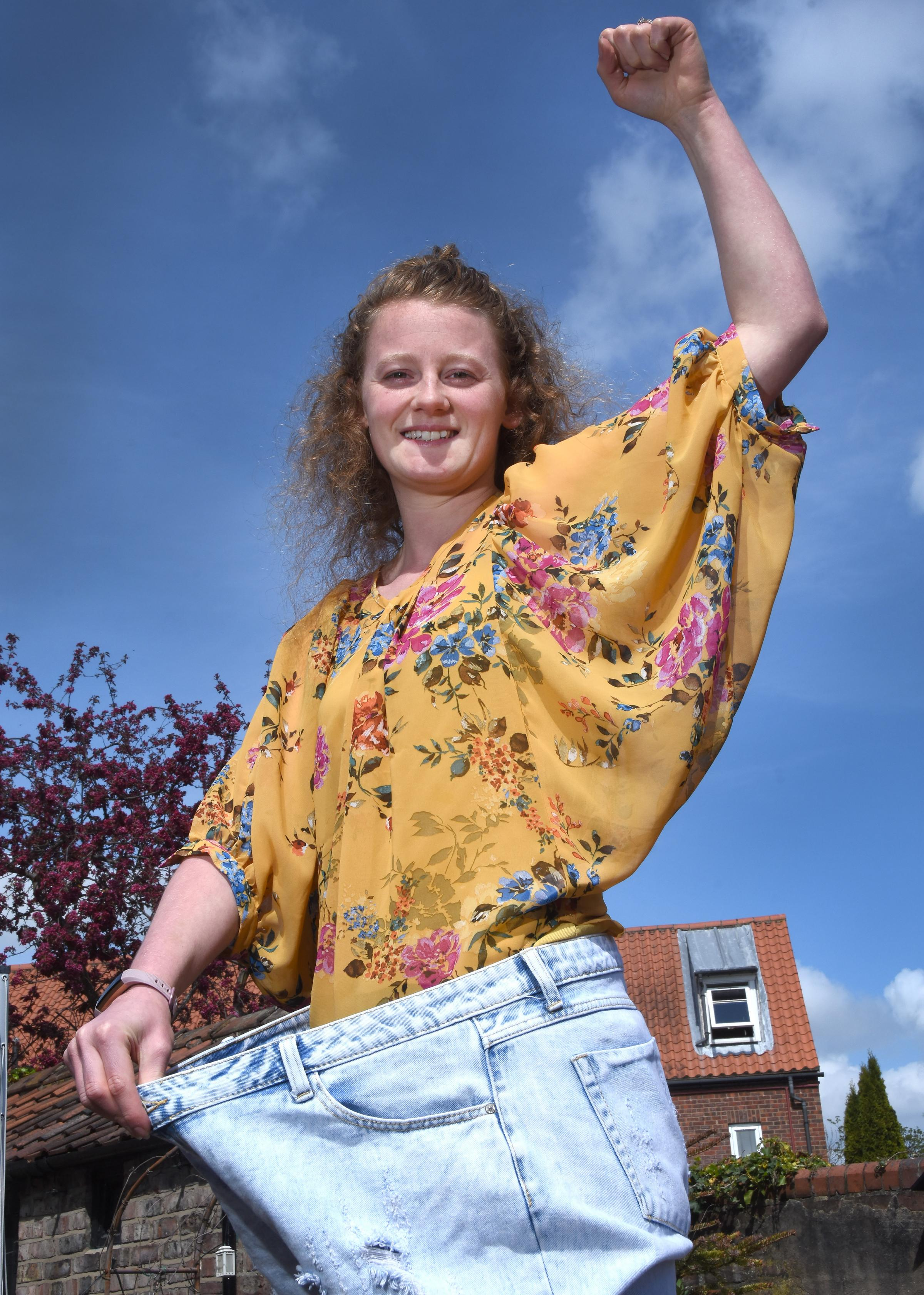 Izzie East, who is doing a skydive in July to raise money for the Yorkshire Air Ambulance after losing six stone to make the jump possible. Izzie is pictured in  one of her old pairs of jeans Picture: David Harrison
