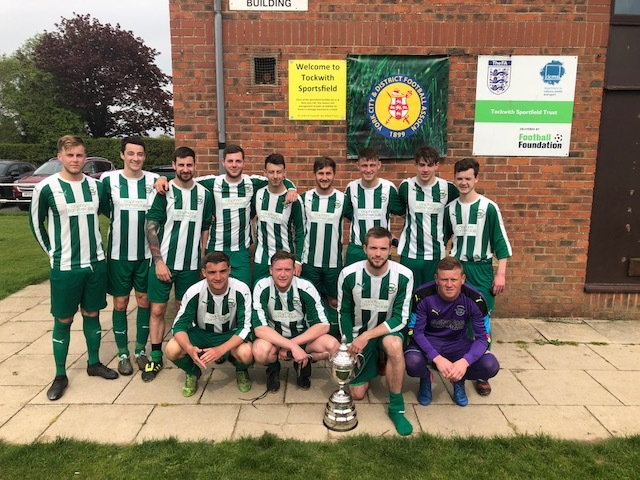 EARNING THEIR STRIPES: York Minster Engineering League champions Wigginton Grasshoppers celebrate winning the York FA Senior Cup following a 5-1 victory over Huntington Rovers