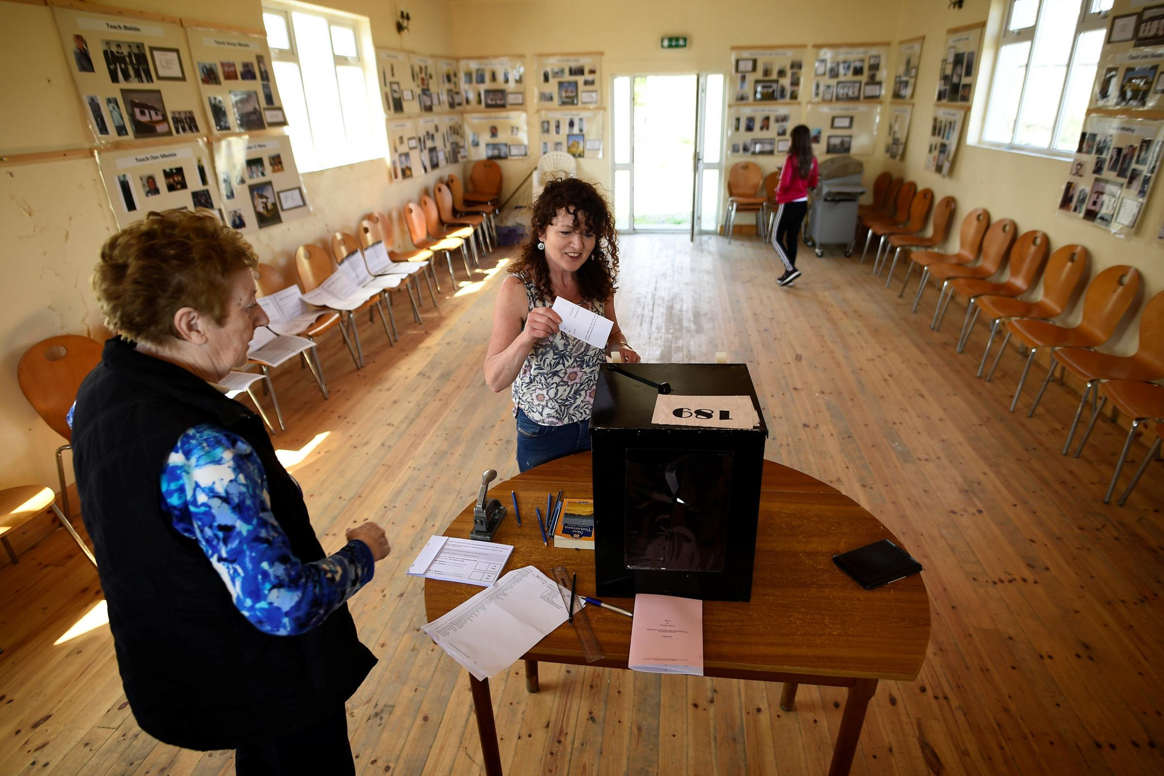 Presiding Officer Carmel McBride looks on as a voter casts their vote in the abortion referendum (Clodagh Kilcoyne/PA)