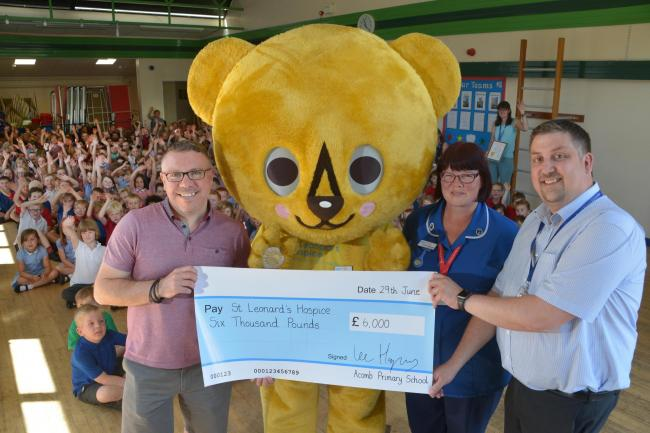 Staff and pupils at Acomb Primary School in York hand over a cheque to St Leonard's Hospice staff and mascot Lenny the Bear